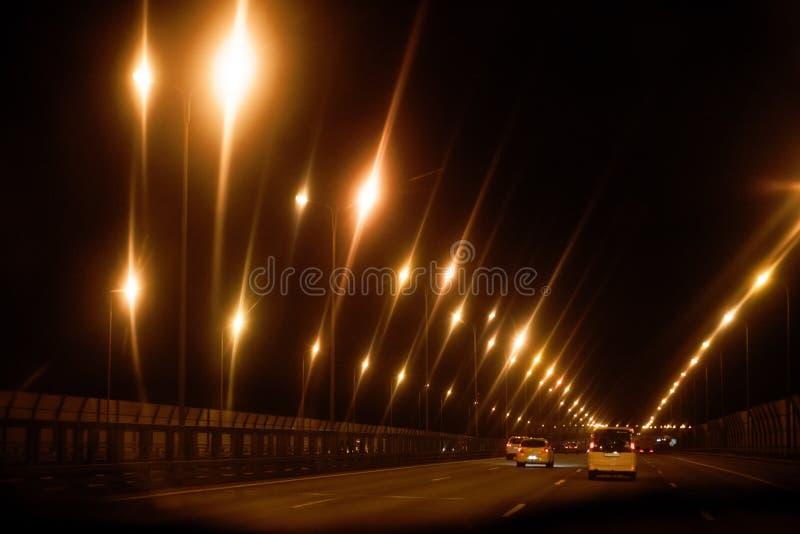 Route noire de route de nuit avec les lumières jaunes photos libres de droits