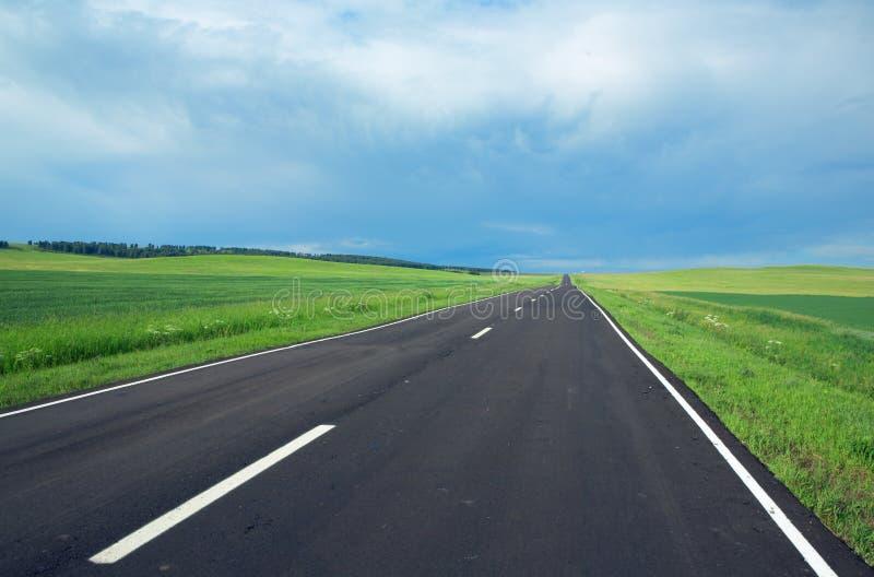 Route, nuages et le ciel bleu photos libres de droits