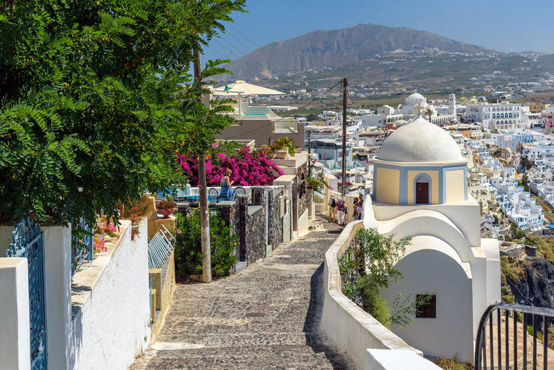 Route pierreuse à la ville de Thira parmi des églises et des maisons traditionnelles sur l'île de Santorini, Grèce photos stock
