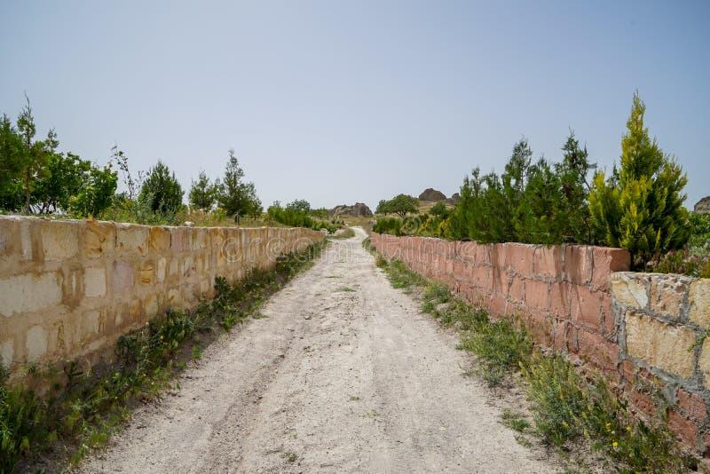 Route rugueuse non pavée de marche de sable par le bas mur de brique en pierre parmi le paysage de la vallée rouge antique sèche  photographie stock