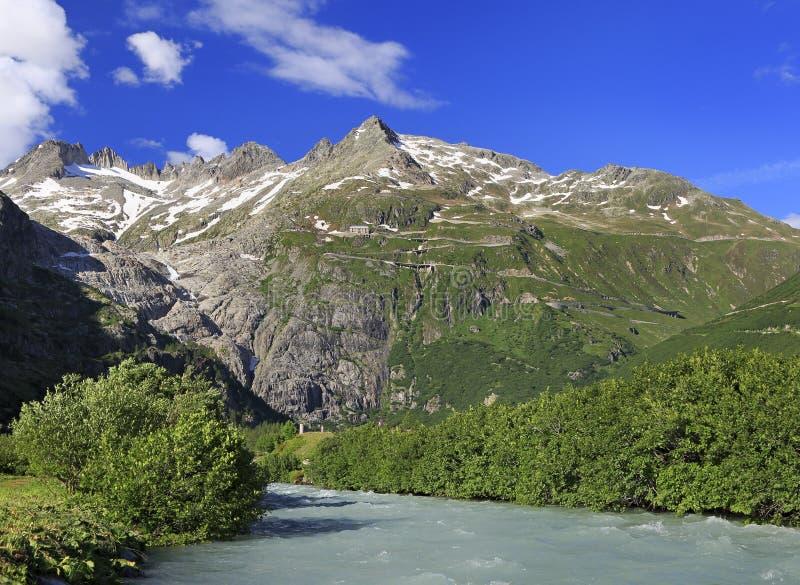 Route serpentine reliant les passages alpins Furka et Grimsel dans les Alpes suisses au Rhône sur le premier plan photos stock