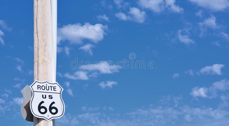 Route 66 sign on blue sky with clouds. stock photo