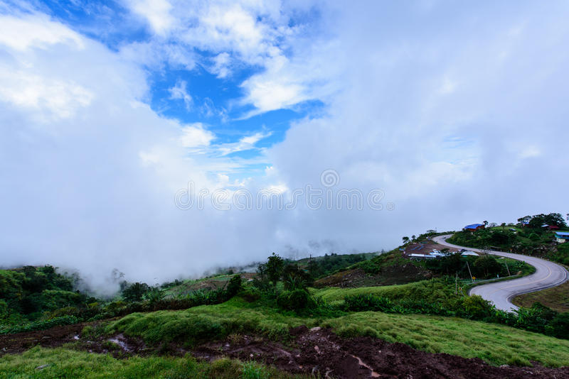 Route under blue sky with morning fog at the mountain view royalty free stock image