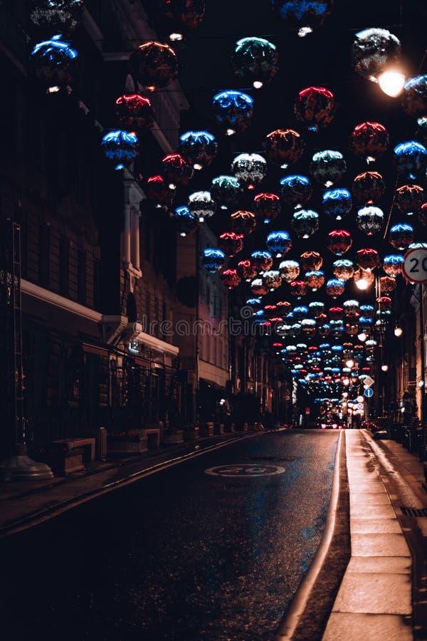 Route urbaine de nuit avec les décorations légères colorées photo stock