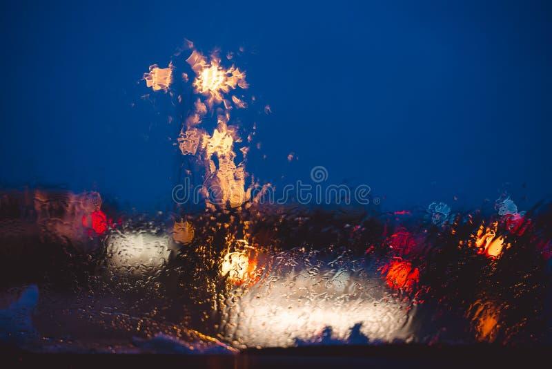 Route urbaine de nuit par la baisse abstraite de l'eau de fond de voitures de pare-brise sur les lumières et la pluie en verre photos stock