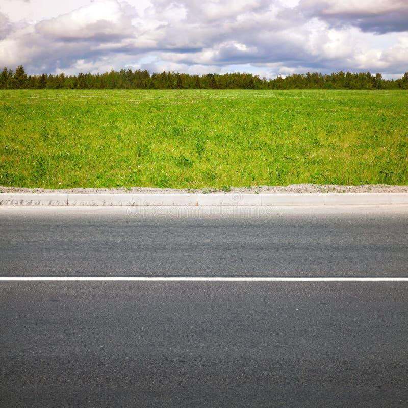Route vide d'été, bord de la route avec l'herbe photo stock