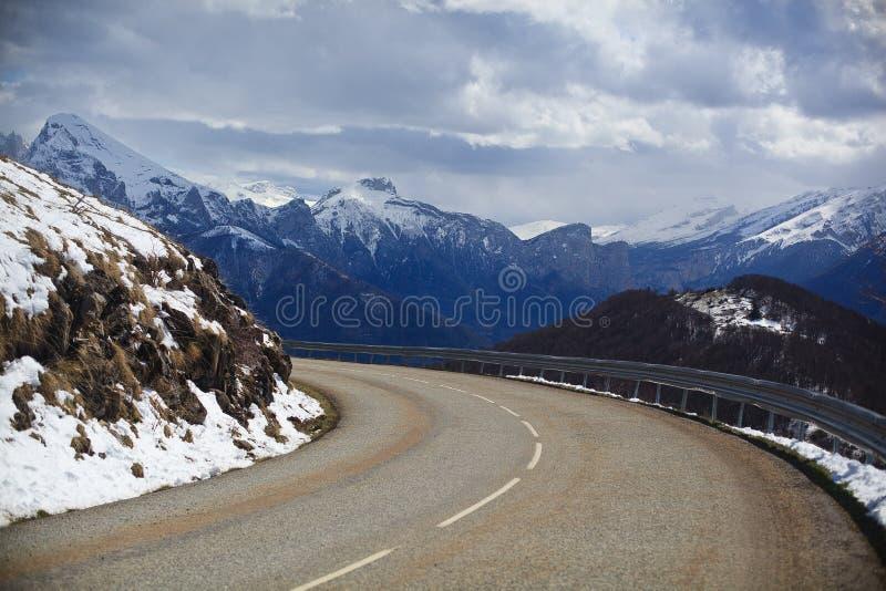 Route vide de montagne sur le fond des crêtes couvertes de neige image stock