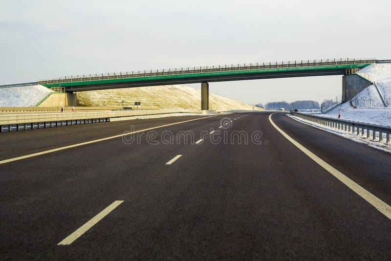 Route vide lisse large moderne d'asphalte s'étendant à l'horizon sous le haut pont tournant à droite la forêt éloignée passée au  photos stock