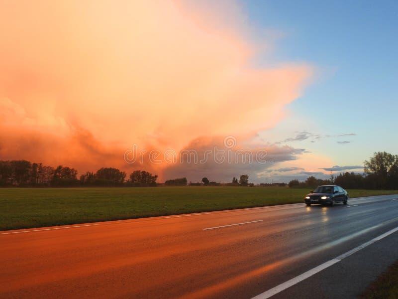 Route, voiture et ciel vif avant pluie dans le temps de lever de soleil, Lithuanie images stock