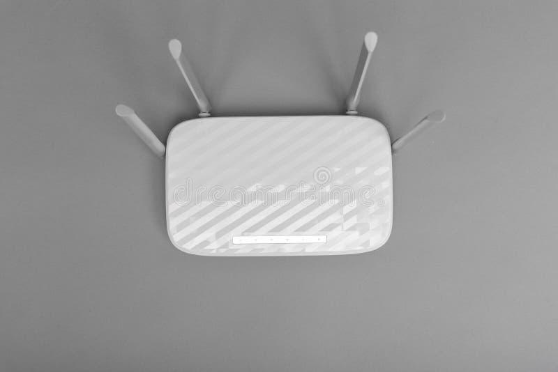 Router moderno branco de Wi-Fi com as quatro antenas no fundo cinzento foto de stock