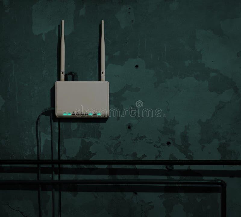 Routeur de Wi-Fi sur un vieux mur dans une chambre noire illustration libre de droits