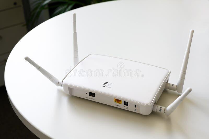 Routeur sans fil d'Internet avec la connexion pour l'Ethernet et la console sur une table blanche dans le bureau, l'espace de cop photos stock