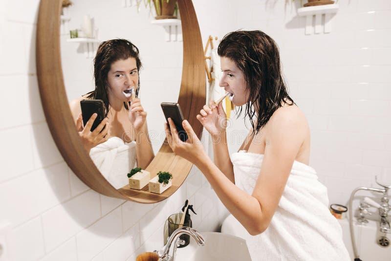 Routine quotidienne de matin Jeune femme heureuse dans des dents de brossage de serviette blanche et regarder l'écran de téléphon photographie stock libre de droits