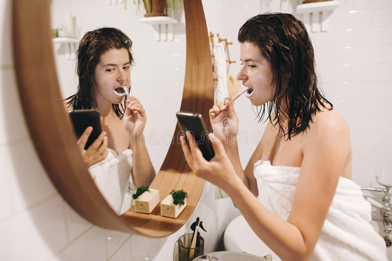 Routine quotidienne de matin Jeune femme heureuse dans des dents de brossage de serviette blanche et regarder l'écran de téléphon photo stock