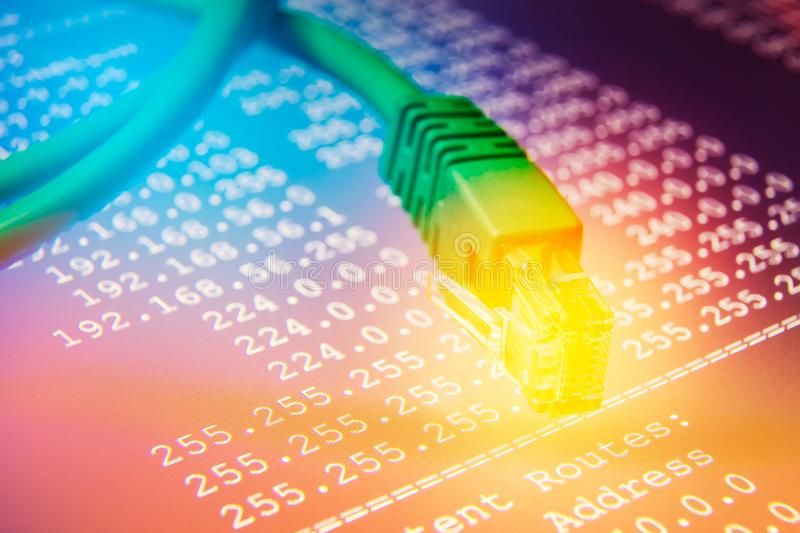 Ethernet cable on routing table, colorful background. Routing table with IP addresses and subnet masks with ethernet cable on colorful background royalty free stock images