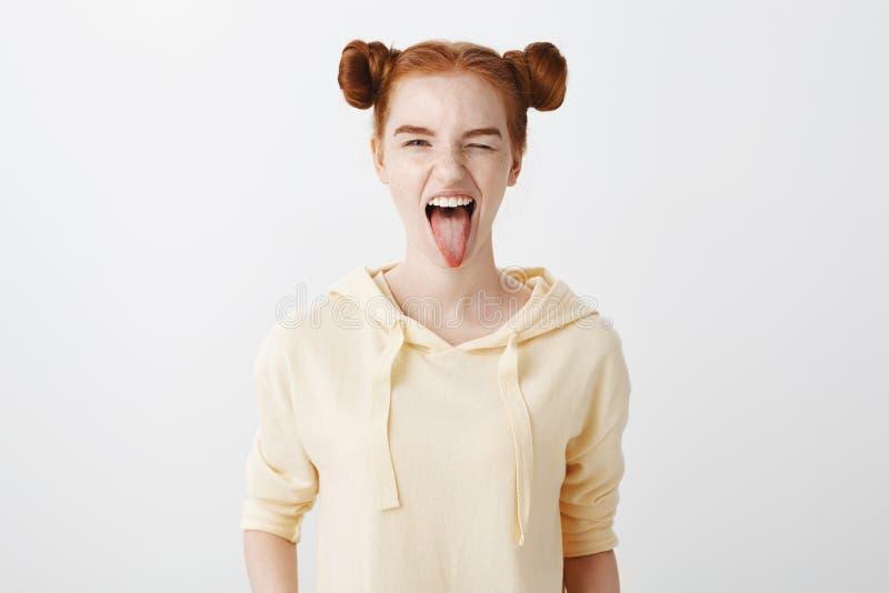 Roux mignon montrent son côté sauvage Tir d'intérieur de fille caucasienne attirante de gingembre avec la coiffure de deux petits photos libres de droits