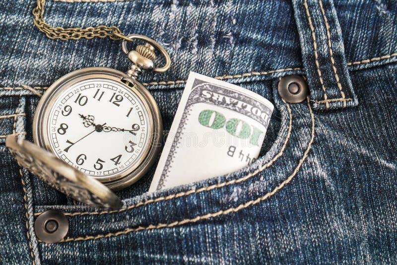 Rova och en dollarräkning i jeans arkivbild