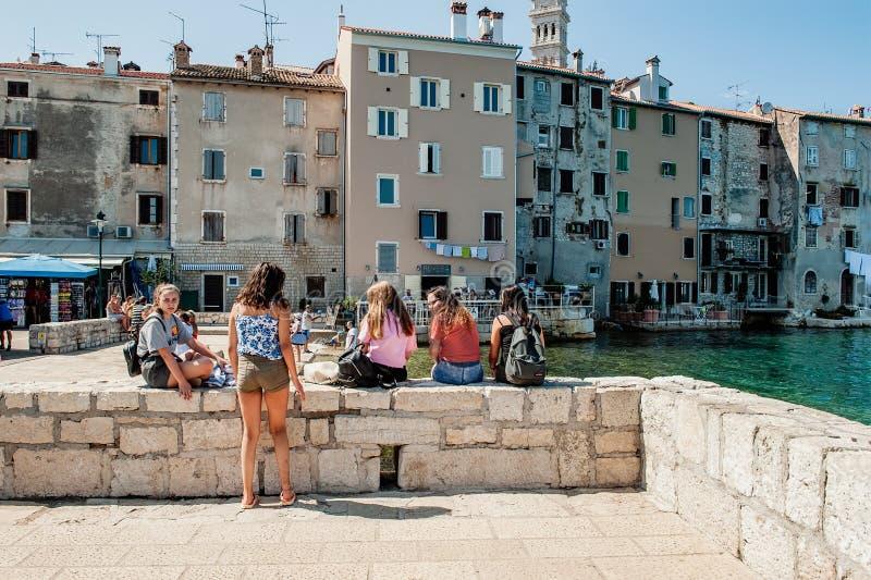 Rovigno, Croazia 30 agosto 2018: Turisti delle ragazze che prendono il sole sui precedenti della città famosa dell'isola Viste e  fotografia stock libera da diritti