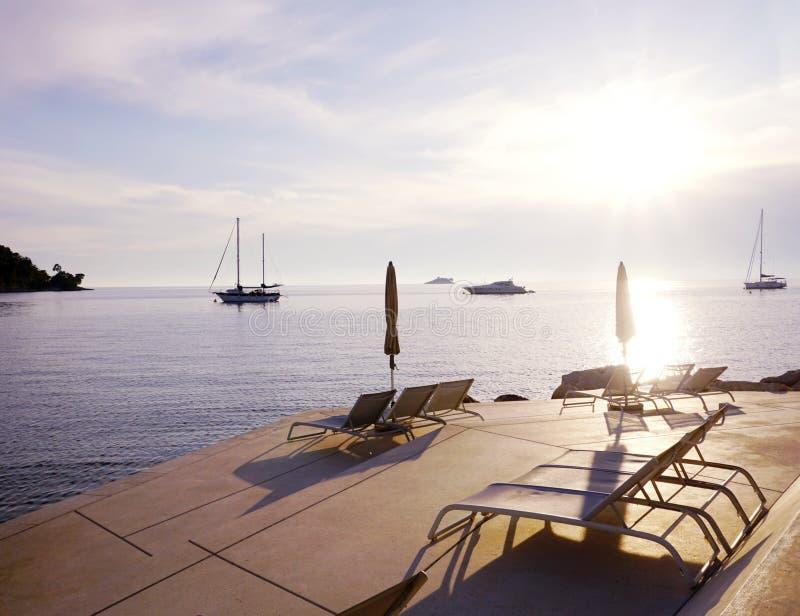 Rovigno, Croazia, il 25 maggio 2019 Spiaggia della località di soggiorno di lusso di estate con le sedie vuote del sole su una sp fotografie stock libere da diritti