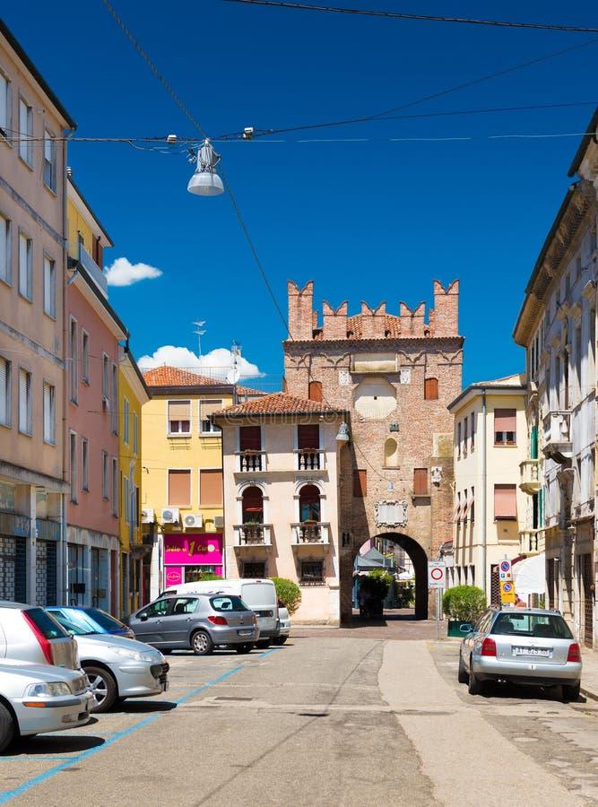 Rovigo, Italië: Mening van de oude toren met boog, omringende gebouwen en geparkeerde auto's stock afbeeldingen