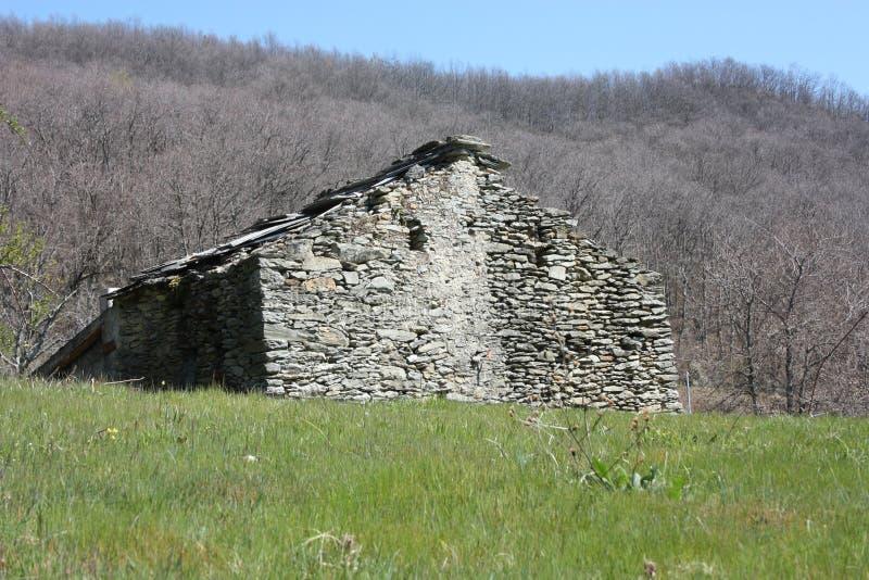 Rovina distrutta una vecchia casa costruita delle pietre abbandonate in uno schiarimento verde, in mezzo alla natura del parco de immagini stock libere da diritti