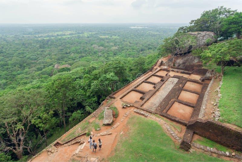 Rovine del palazzo della città antica sulla roccia di Sigiriya e di alcuni turisti che camminano intorno all'area archeologica fotografia stock