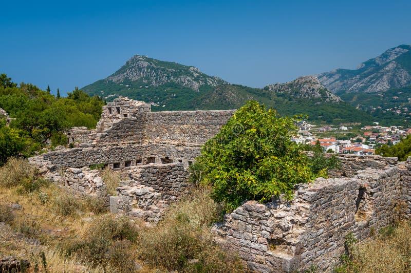 Rovine della fortezza medievale con un fondo della montagna immagini stock libere da diritti