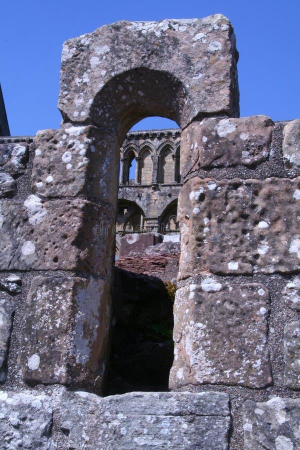 Rovine medievali osservate attraverso una finestra di pietra dell'arco fotografia stock