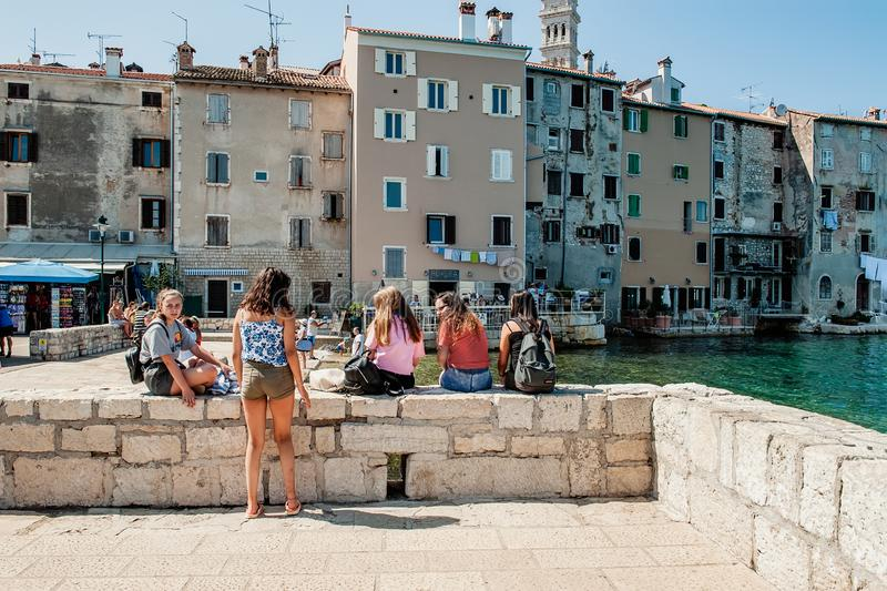 Rovinj, Croatia August 30, 2018: Girls Tourists sunbathing on the background of the famous city of the island. Sights and tourist royalty free stock photo