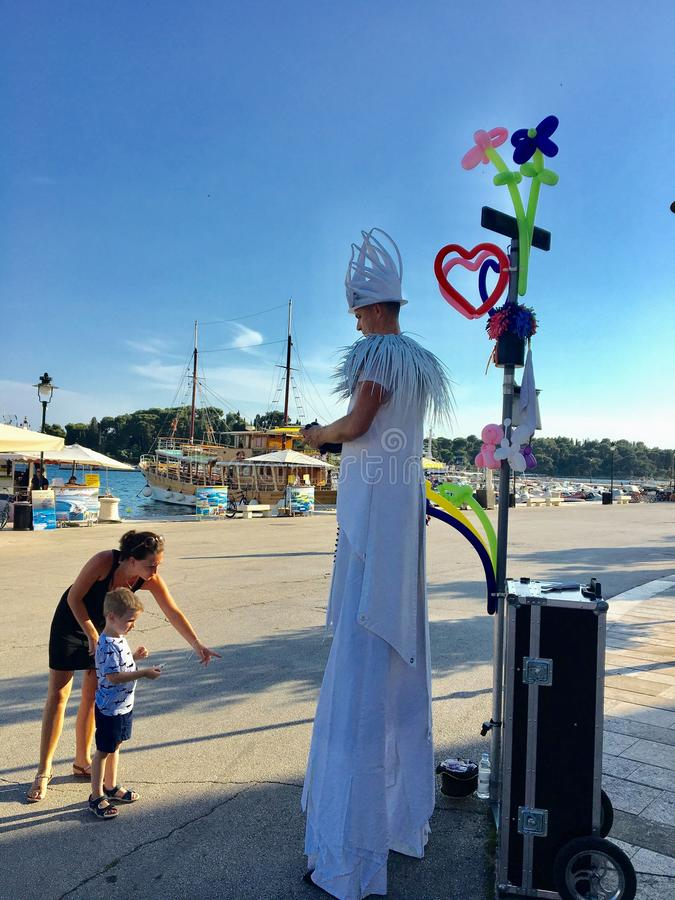 A street performer on stilts making a balloon animal for a small child with his mother beside him. Rovinj, Croatia - July 3rd, 2019: A street performer on stilts stock photos