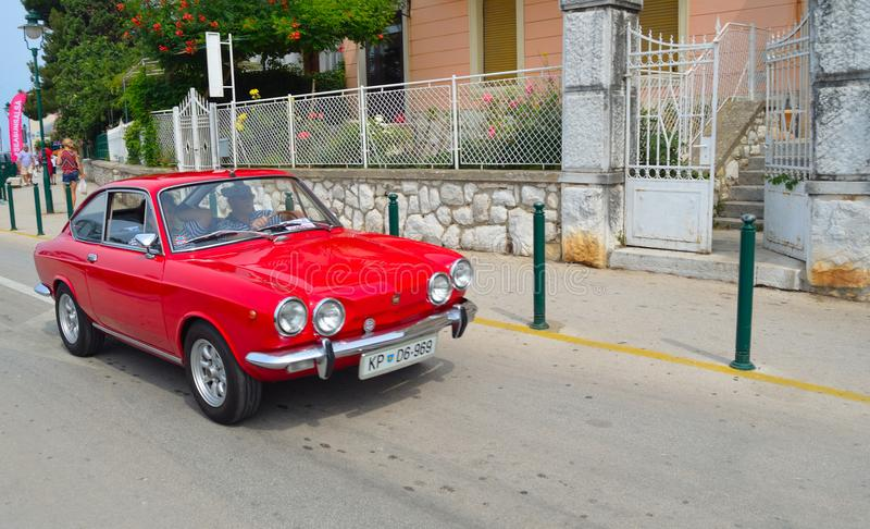 Classic Red Fiat Motor Car being driven along street. royalty free stock images