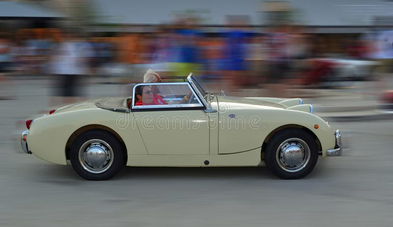 Classic White Austin Healey Frog eye Sprite being driven through town square in Rovinj in tour of Croatia. stock images