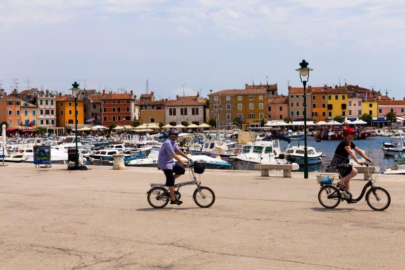 Rovinj Kroatien-Juni 25, 2017: Man och kvinna på en cykel i marina av den gamla staden av Rovinj fotografering för bildbyråer