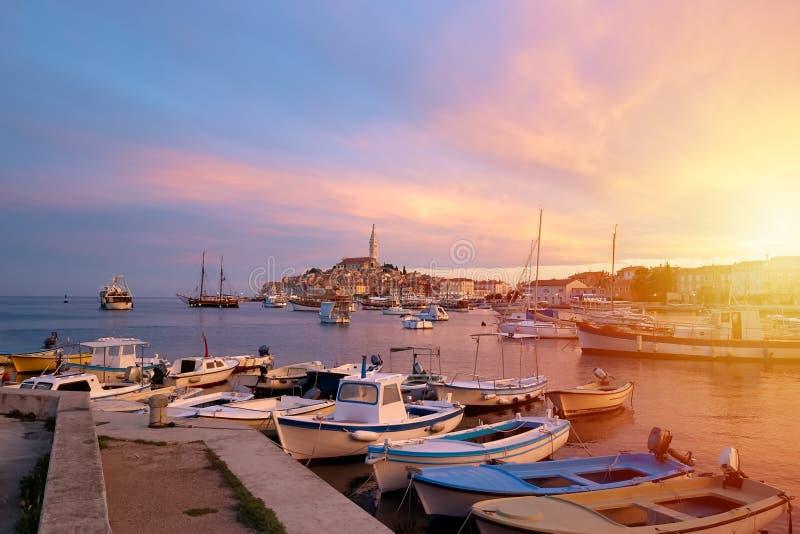 Rovinj, oude ribbenstad van Kroatië in gouden zonsopganglicht Motorboten, boten en jachten op water in haven van Rovinj Hoge tore stock foto
