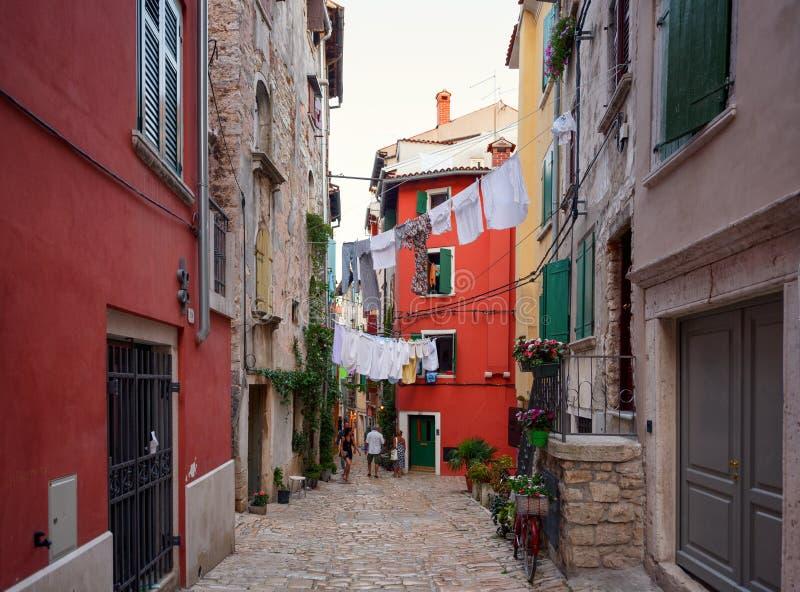 Narrow cobblestone street with hanging laundry in Rovinj, Istria, Croatia royalty free stock photo