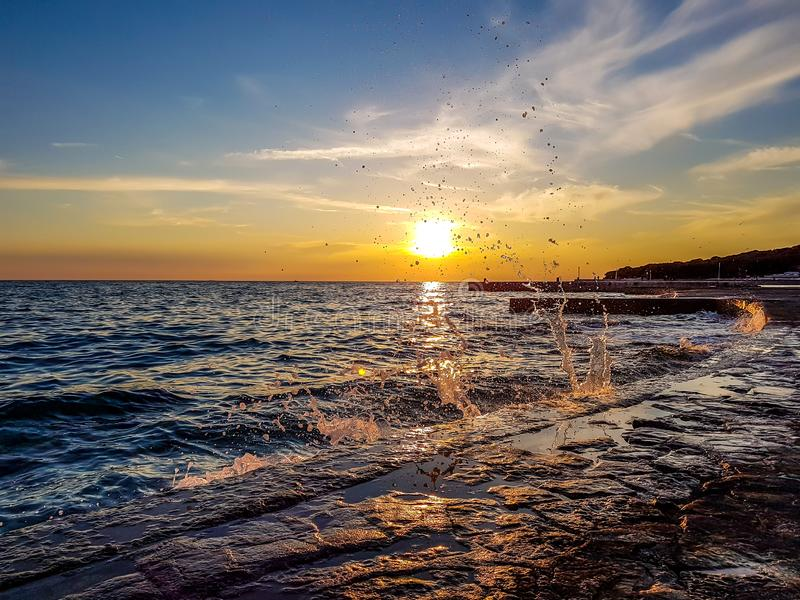 Rovinj - Waves splashing in the harbour by the sunset. Romantic sunset by a stony harbor promenade. The sun sets over the horizon. The sunbeams reflecting in the royalty free stock images