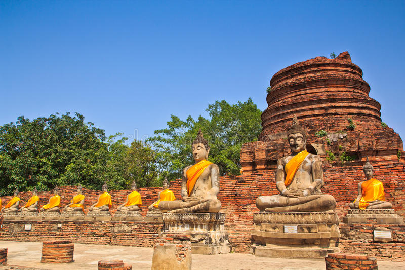 A row of ancient buddha statues in front of ruin pagoda. Buddha statues in Ayutthaya province of Thailand stock photos