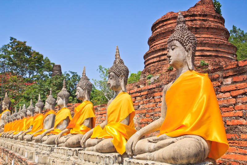 A row of ancient buddha statues in front of ruin pagoda. Buddha statues in Ayutthaya province of Thailand royalty free stock photos
