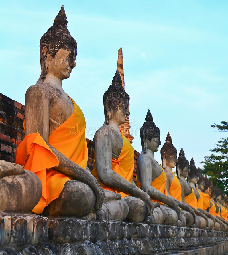 A row of ancient buddha statues in front of ruin pagoda. Buddha statues in Ayutthaya province of Thailand royalty free stock photography