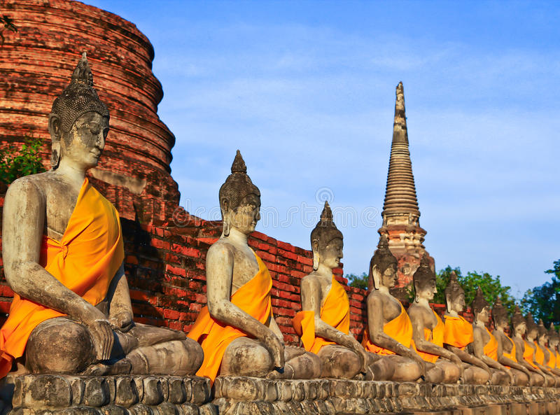 A row of ancient buddha statues in front of ruin pagoda. Buddha statues in Ayutthaya province of Thailand stock photo