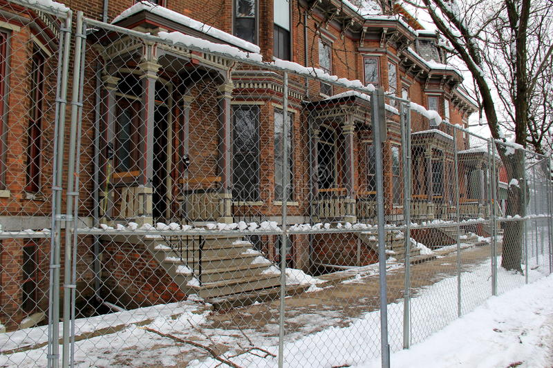 Row of apartment buildings being renovated,chain-link fencing outside. Row of old brick apartment buildings being gutted and then renovated, chain-link fencing royalty free stock images