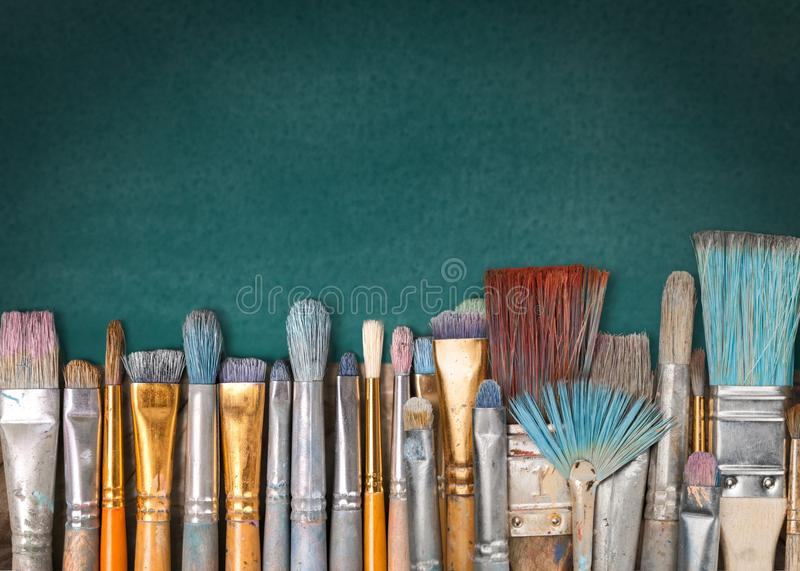 Row of artist paint brushes on green background. Row art paint artistic artist brushes green stock photos