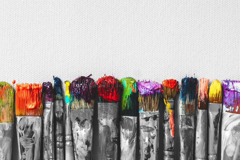 Row of artist paintbrushes with colorful bristle closeup royalty free stock photo