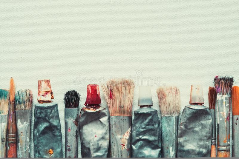 Row of artist paintbrushes and paint tubes closeup on artistic canvas. stock photo