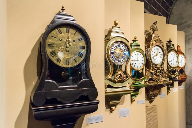 Row of assorted pendulum mantel clocks. Row of assorted old historic pendulum mantel clocks mounted on a receding wall with information plates below in an stock images