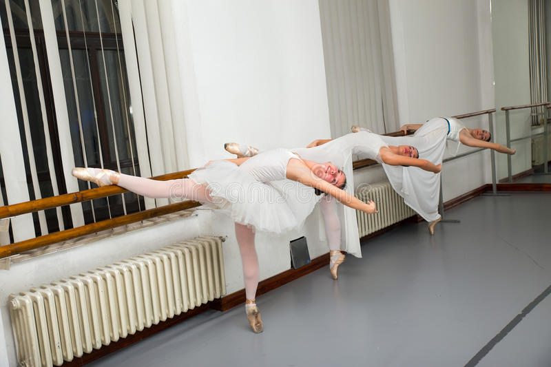 Row of ballet dancers practicing at barre in rehearsal room. Row of female ballet dancers practicing at barre in rehearsal room stock photo