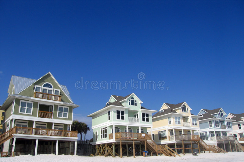 Row of Beach Homes. A row of pastel colored beach cottages against a brilliant blue sky on a white sand beach