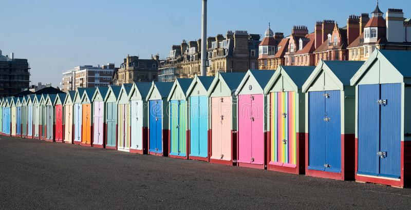 A row of Beach huts Brighton and Hove. A line of twenty five multi coloured beach huts on Brighton promenade with a diminishing perspective, the sun is shining stock photography