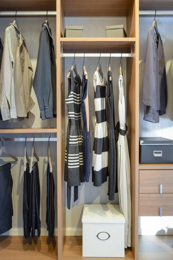 Row of black dress,shirts and pants hang in wardrobe. Row of black dress,shirts and pants hang in wooden wardrobe stock images