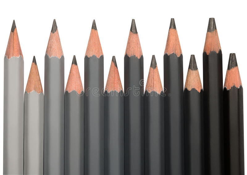 Row of black graphite pencils with different hardness. Colored from light grey to black stock image